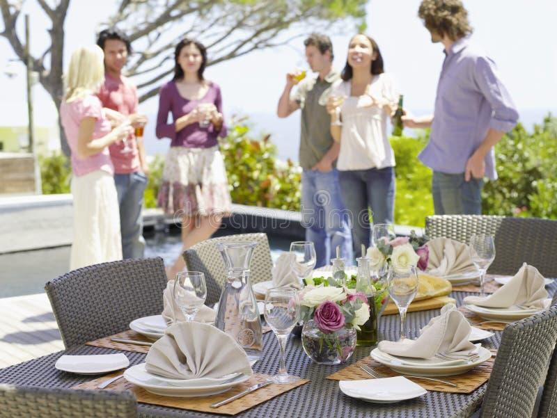 Regolazione fine del tavolo da pranzo con gli amici nel fondo fotografia stock