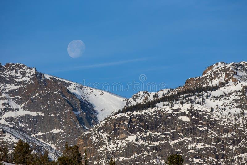 Regolazione gibbous calante della luna dietro i picchi di montagna nevosi immagini stock libere da diritti