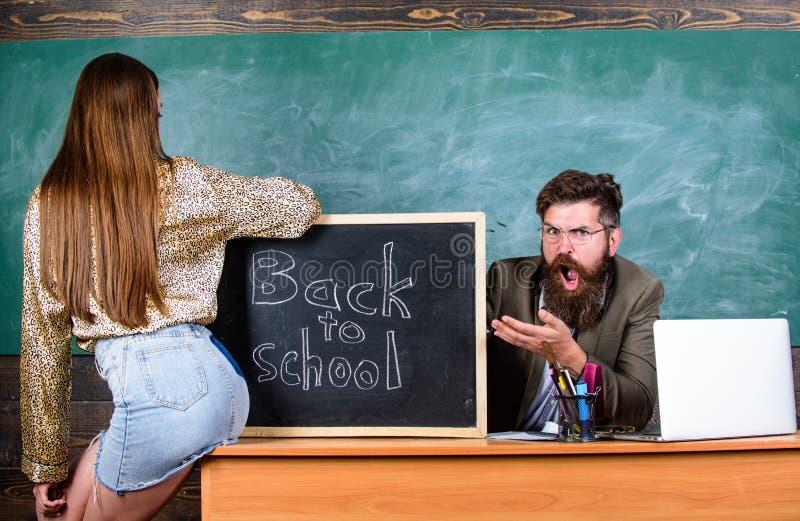 Regras da disciplina e do comportamento da escola O professor indignante senta o fundo do quadro da tabela Estudante na mini saia imagem de stock royalty free