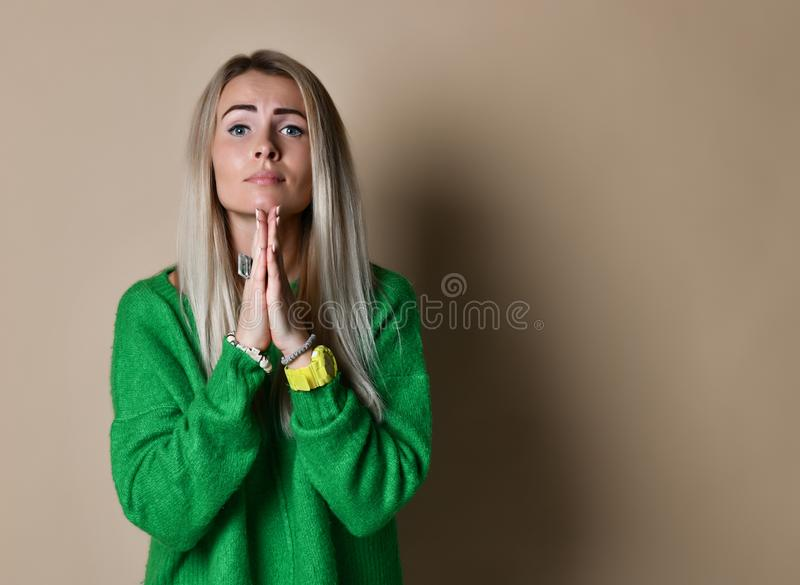 regretful woman looks gloomy and desperate, keeps palms together, beggs for forgiveness in boyfriend as betrayed him stock photos