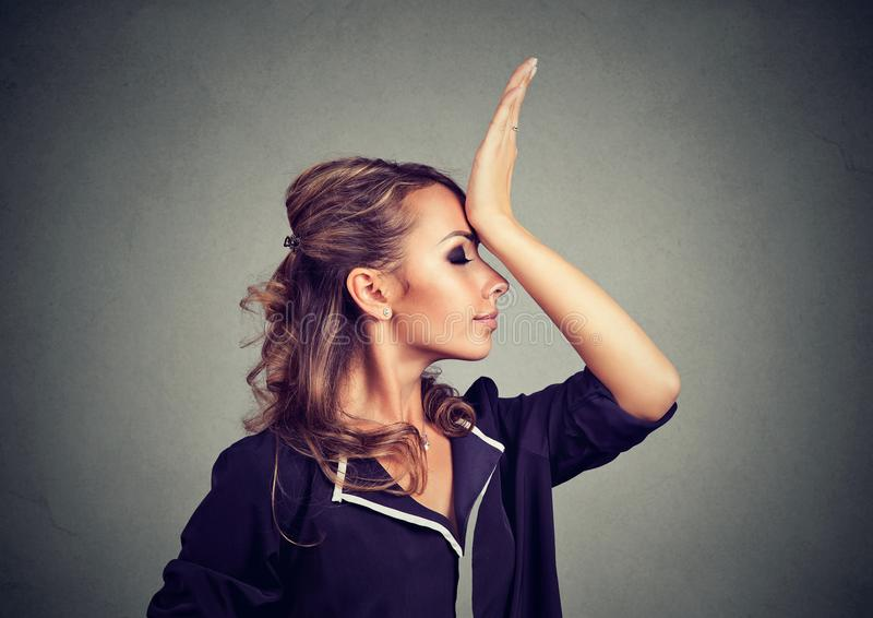 Regrets wrong doing. Sad woman, slapping hand on head having duh moment isolated on gray background. royalty free stock photography