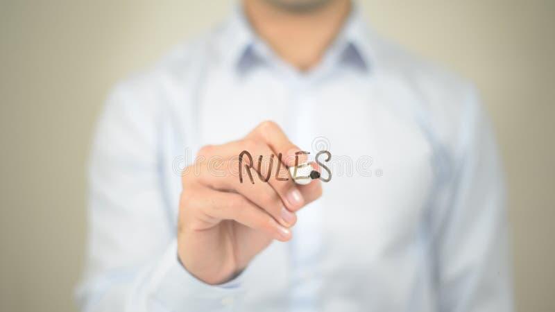 Reguły, mężczyzna writing na przejrzystym ekranie zdjęcie stock
