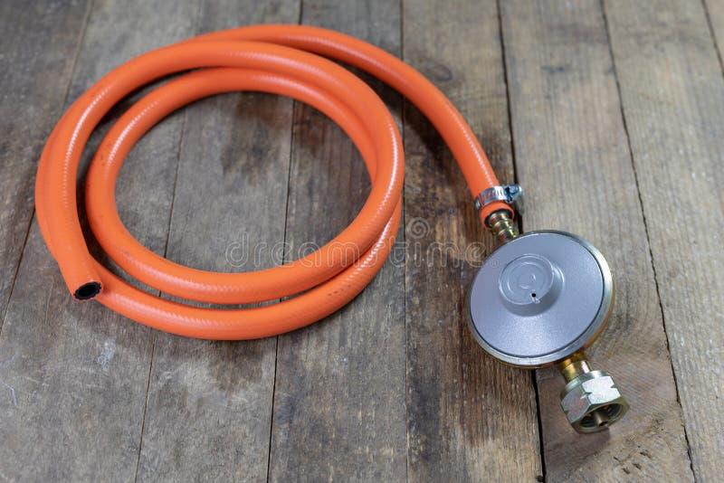Regulador para el cilindro y los accesorios de gas del propano-butano en un w foto de archivo