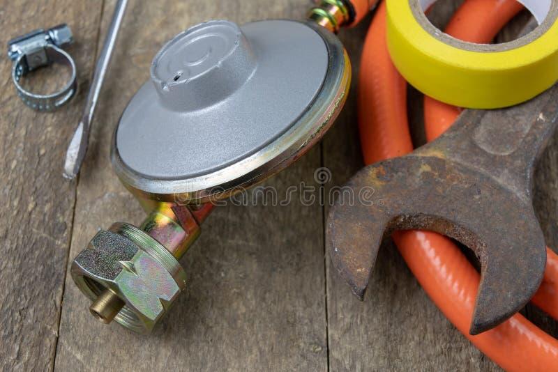 Regulador para el cilindro y los accesorios de gas del propano-butano en un w fotos de archivo