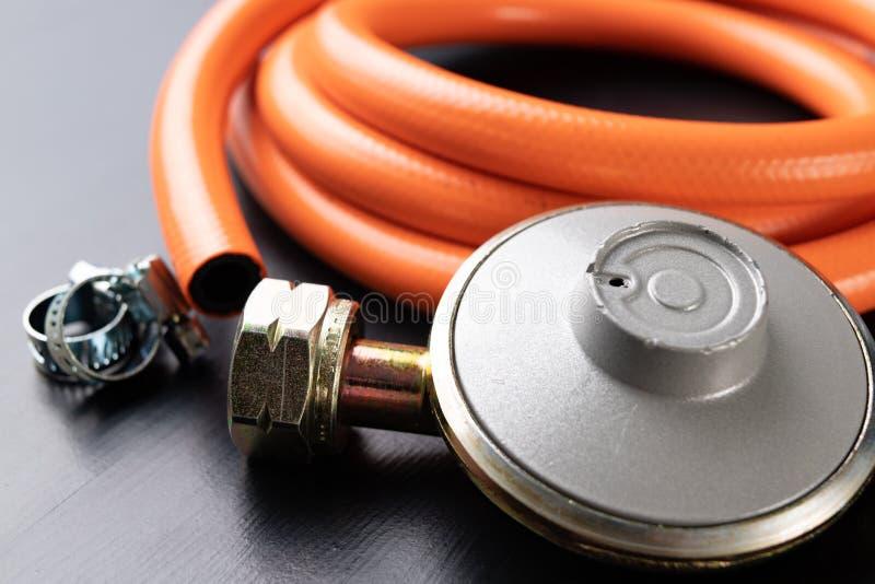 Regulador para el cilindro y los accesorios de gas del propano-butano en una tabla de madera del taller Accesorios del gas en el  imagen de archivo libre de regalías