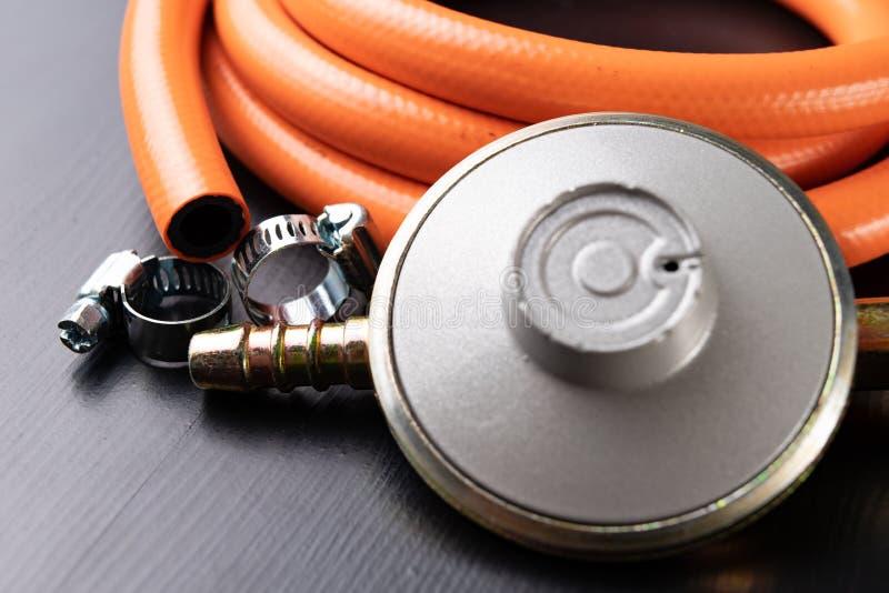Regulador para el cilindro y los accesorios de gas del propano-butano en una tabla de madera del taller Accesorios del gas en el  fotos de archivo