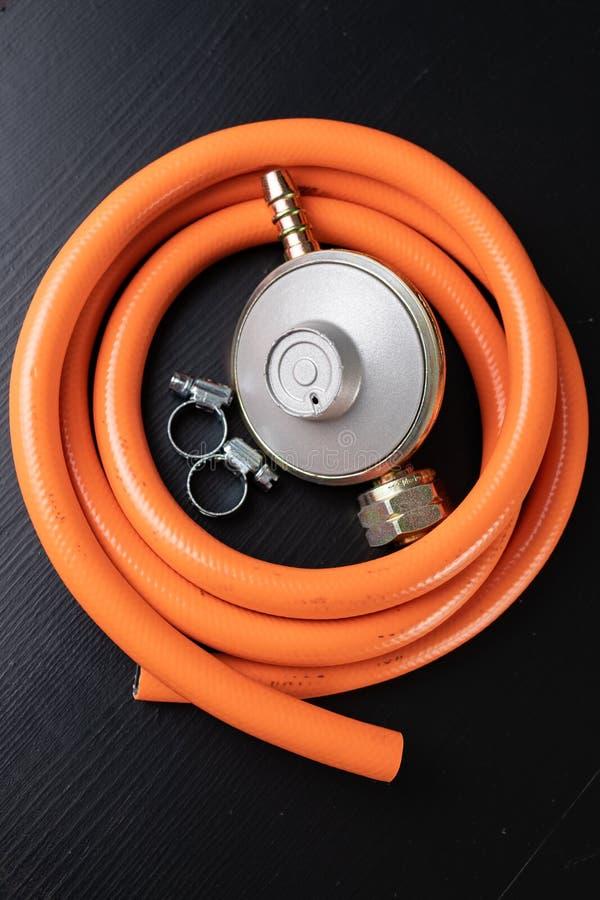 Regulador para el cilindro y los accesorios de gas del propano-butano en una tabla de madera del taller Accesorios del gas en el  fotografía de archivo libre de regalías