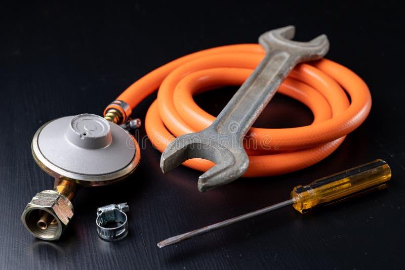 Regulador para el cilindro y los accesorios de gas del propano-butano en una tabla de madera del taller Accesorios del gas en el  imagenes de archivo