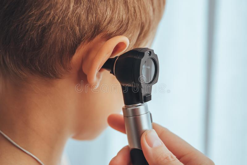 Regular doctor visit health check up. Doctor checking ear with Optic Otoscope to boy. royalty free stock photography