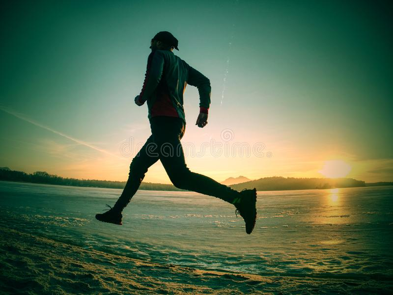 Regular winter workout. Run by frozen river on sandy beach. Regular winter workout. Runner run by frozen river on sandy beach. Orange sun close hilly horizon in stock photos