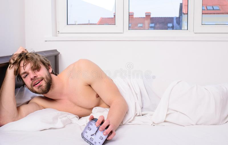 Regulate your bodys clock. Man unshaven tousled hair wakeful face having rest. Good morning. Man unshaven lay bed hold. Alarm clock. Stick schedule same bedtime stock images