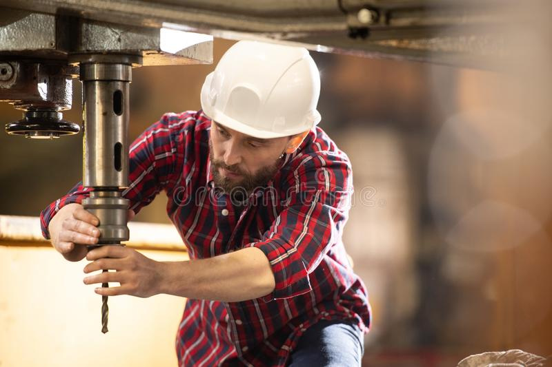 Regulating drilling element. Young technician in hardhat and overalls putting drill element into iron holder which is part of large industrial machine royalty free stock images