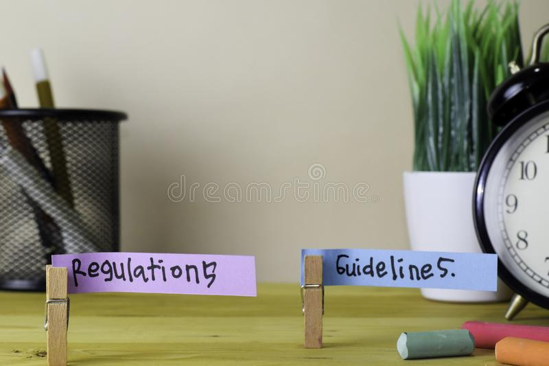 Regulations and Guidelines. Handwriting on sticky notes in clothes pegs on wooden office desk stock photography