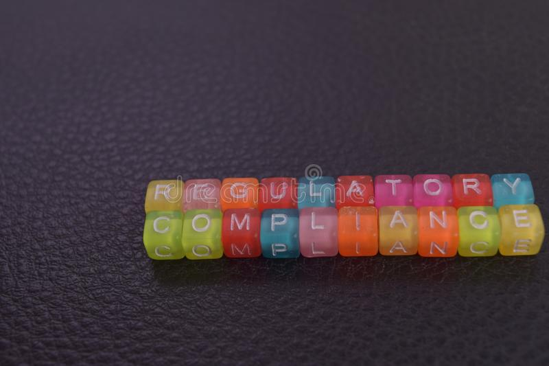Regulatory Compliance on wooden blocks. Cross processed image with business concept on black background stock image