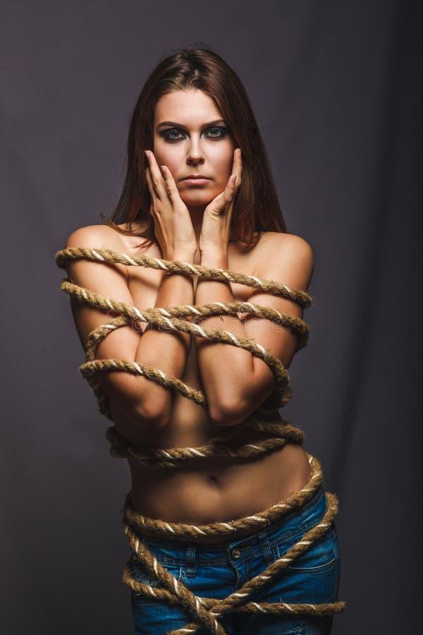 Rehén moreno, mujer encuadernada del cautivo con el preso de la cuerda en mezclilla imagen de archivo