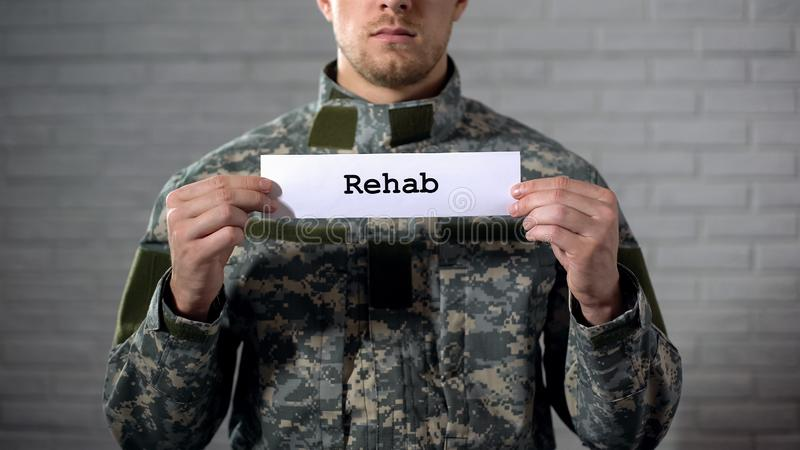 Rehab word written on sign in hands of male soldier, military disorder, health. Stock photo royalty free stock photography
