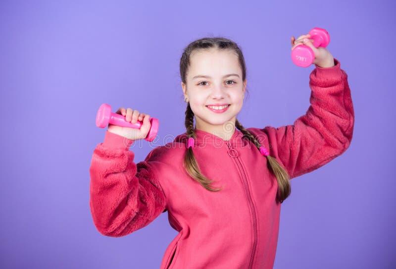 Rehabilitatieconcept meisje dat met domoor uitoefent Kindgreep weinig domoor violette achtergrond Beginnersdomoor stock afbeeldingen
