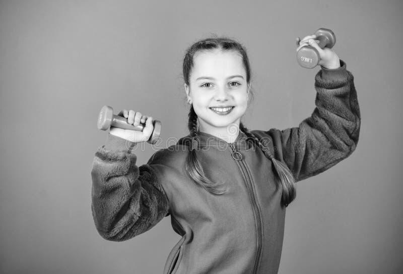 Rehabilitation concept. Girl exercising with dumbbell. Child hold little dumbbell violet background. Beginner dumbbell royalty free stock images