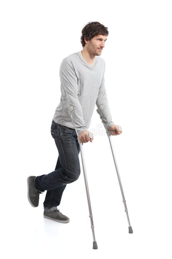 Rehabilitation eines erwachsenen Mannes, der mit Krücken geht stockbild