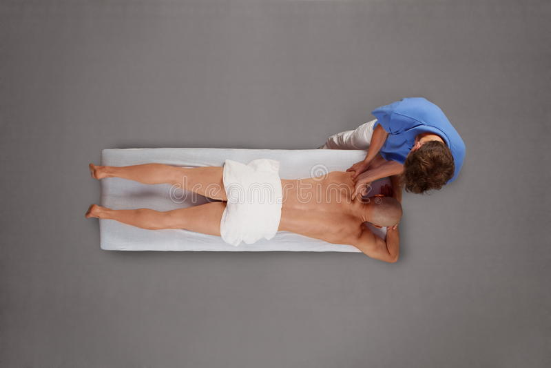 Rehabilitation - Mann, der vom Therapeuten massiert wird lizenzfreie stockbilder
