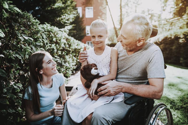Rehabilitation With Wheelchair. Caregiver with Man. Walk on Nature with Family and Young Girl. Happy Old Man and Woman with Child. Professional Caregiver with royalty free stock photo