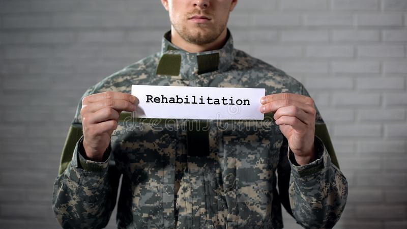 Rehabilitation word written on sign in hands of male soldier, health support. Stock photo royalty free stock image
