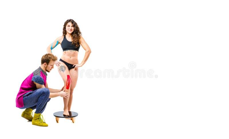 Rehabilitering för temakinesiologyband och hälsa av idrottsman nen Den härliga flickan står på en vit bakgrund, man arkivbild