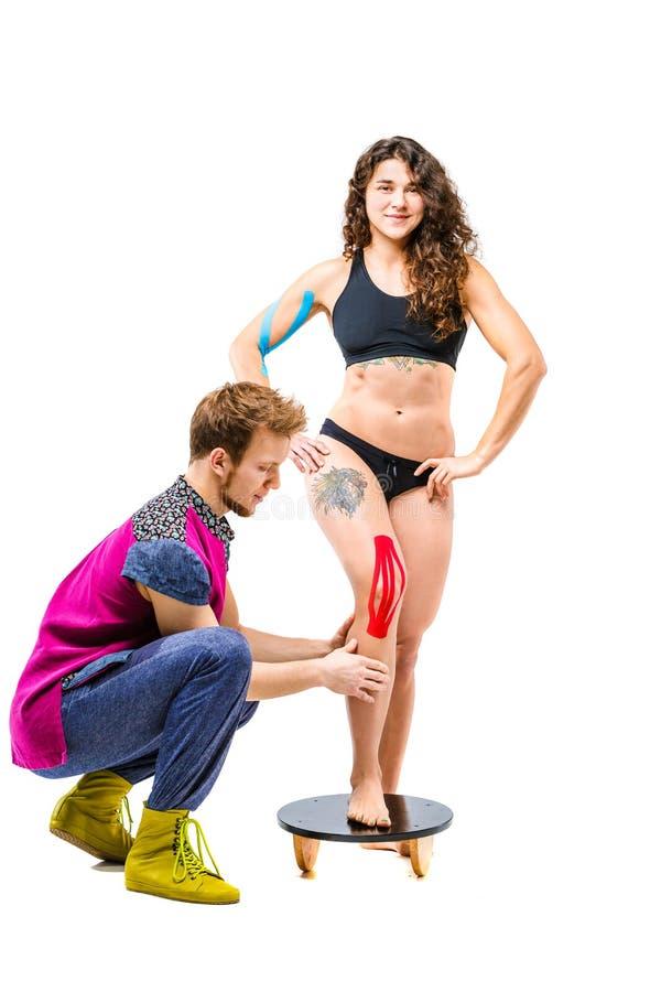 Rehabilitering för temakinesiologyband och hälsa av idrottsman nen Den härliga flickan står på en vit bakgrund, manligt terapeutd royaltyfri foto
