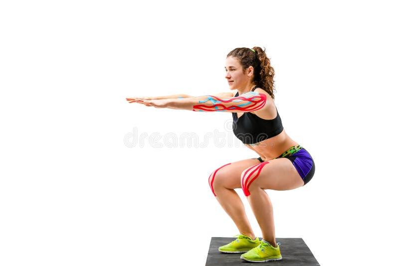 Rehabilitering för temakinesiologyband och hälsa av idrottsman nen Härlig flicka som gör en satt övning på en svart filt på en vi fotografering för bildbyråer