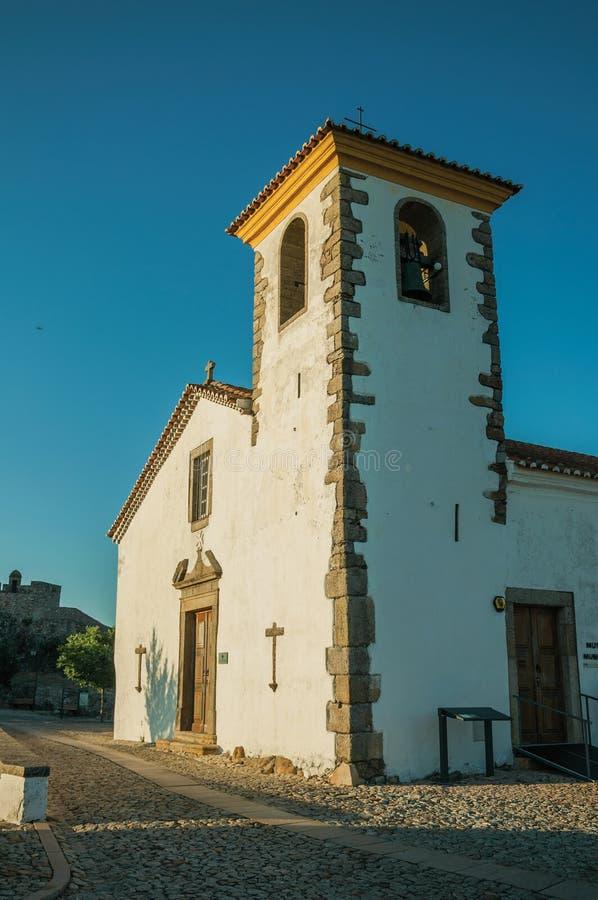 Rehabilitierte Wand in der alten Kirche mit Kirchturm und Holztür stockfoto