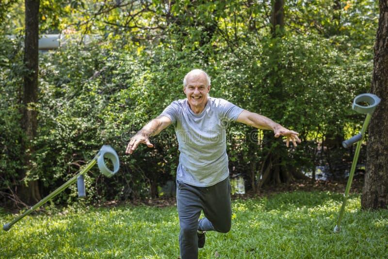 Rehabilitierter älterer Mann, der seine Krücken wirft stockfoto