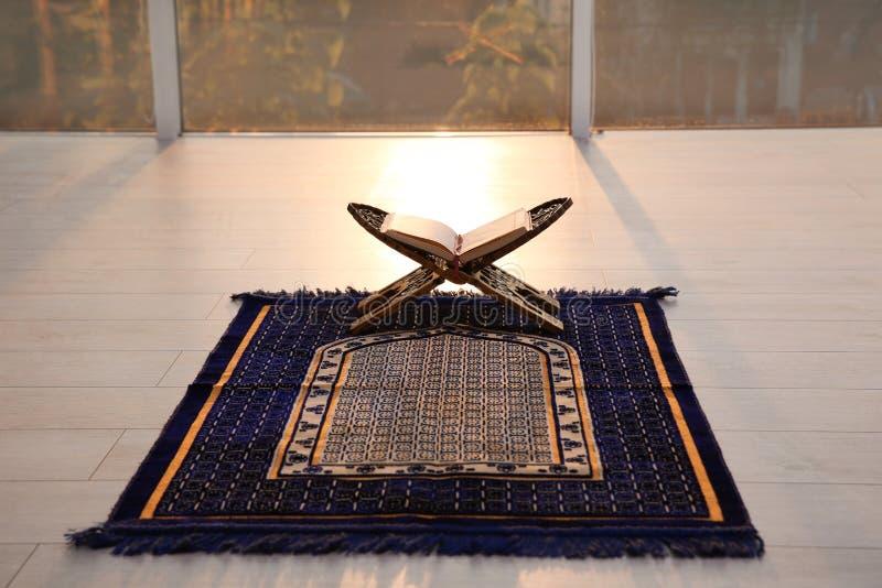 Rehal com o Corão aberto no tapete de oração muçulmano foto de stock