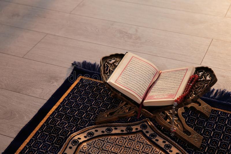 Rehal with open Quran and Muslim prayer beads on rug indoors stock photography