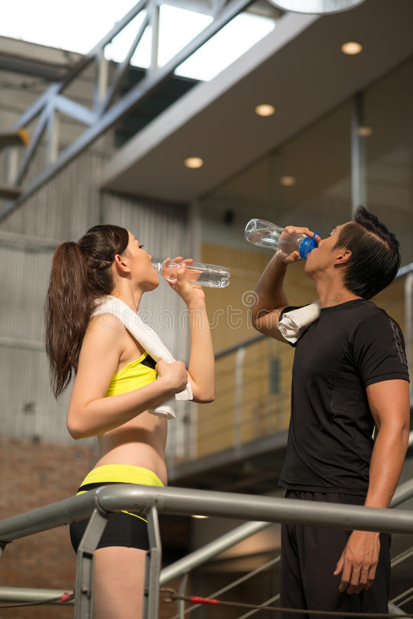 Rehydration. Asian couple drinking fresh water after training royalty free stock photo