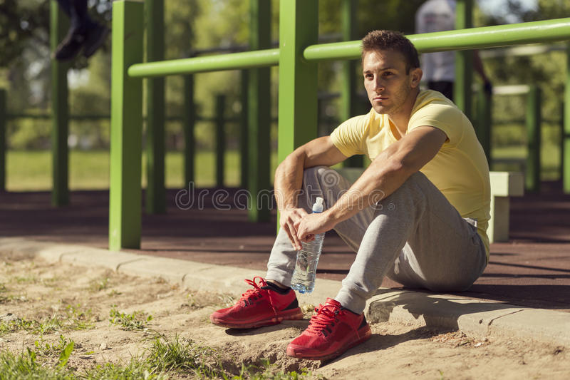 Rehydration. Athlete relaxing after an intense workout, holding a bottle of water royalty free stock photos