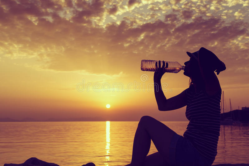 Rehydration. Young woman sitting on the rocky shore, drinking water and enjoying a beautiful sunset in Syvota bay, Greece stock photo