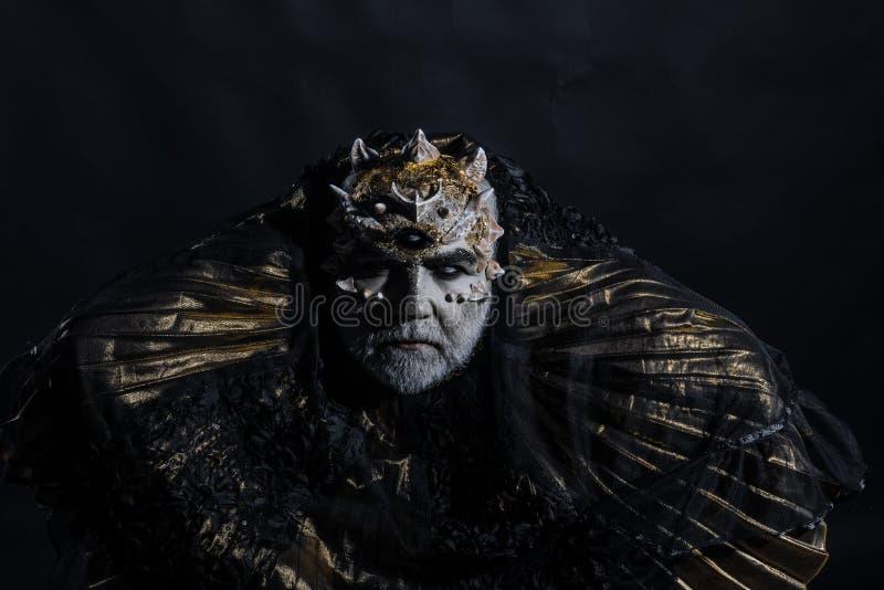 Rei antigo do mundo do conto de fadas que senta-se no trono, conceito da fantasia Espinhos farpados velhos do homem cego em sua c imagem de stock