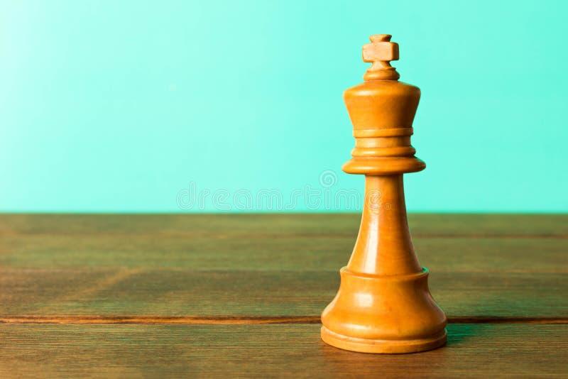 Rei da xadrez em uma tabela de madeira Em um fundo de turquesa U próximo imagem de stock royalty free