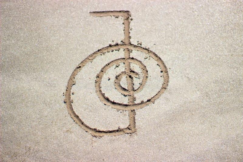 Rei del ku del cho del símbolo de la curación de Reiki en la arena imagen de archivo