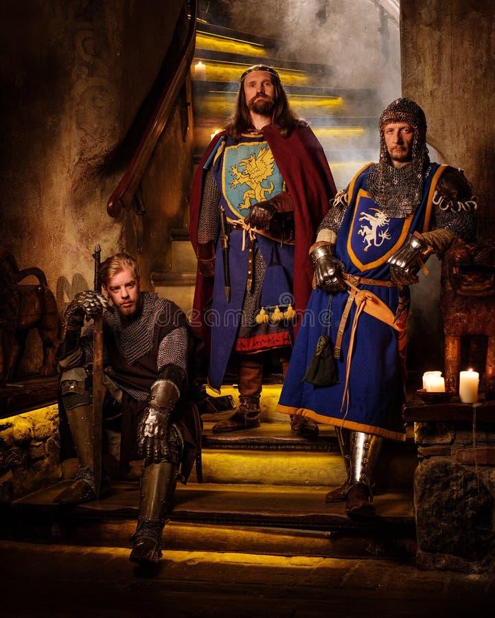 Rei medieval com seus cavaleiros no interior antigo do castelo fotos de stock royalty free