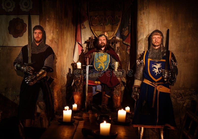 Rei medieval com seus cavaleiros no interior antigo do castelo imagens de stock royalty free