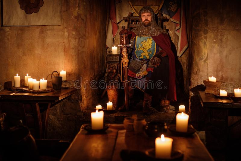 Rei medieval idoso no trono no interior antigo do castelo foto de stock royalty free