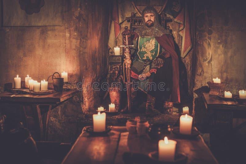 Rei medieval no trono no interior antigo do castelo fotografia de stock