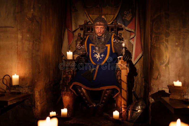 Rei medieval no trono no interior antigo do castelo imagens de stock royalty free