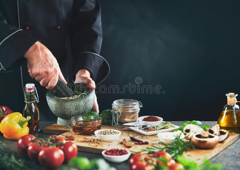 Reibende Kräuter des Chefs nahe bei Gewürzbehältern lizenzfreies stockfoto