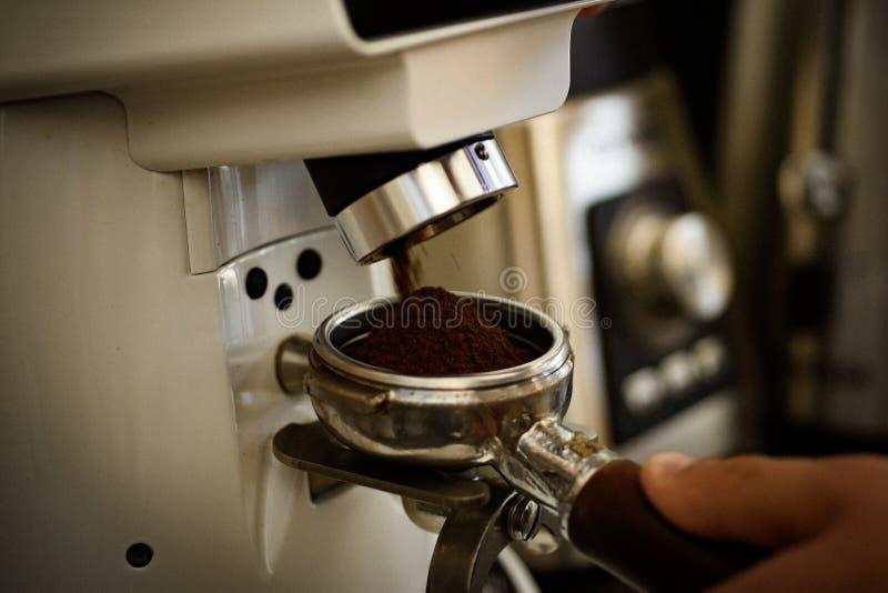 Reibender Berufsmechanismus Barista-Schleifen-Kaffeebohnen unter Verwendung der Kaffeemaschine Kaffeemühle, die gebratene Bohnen  lizenzfreie stockfotos