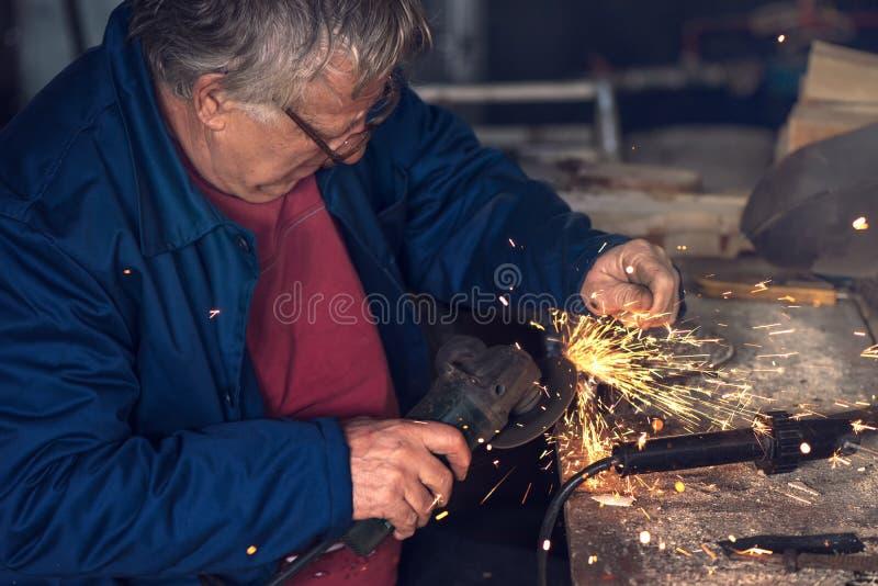 Reibendes Metall der reifen männlichen Arbeitskraft in der Werkstatt stockbilder
