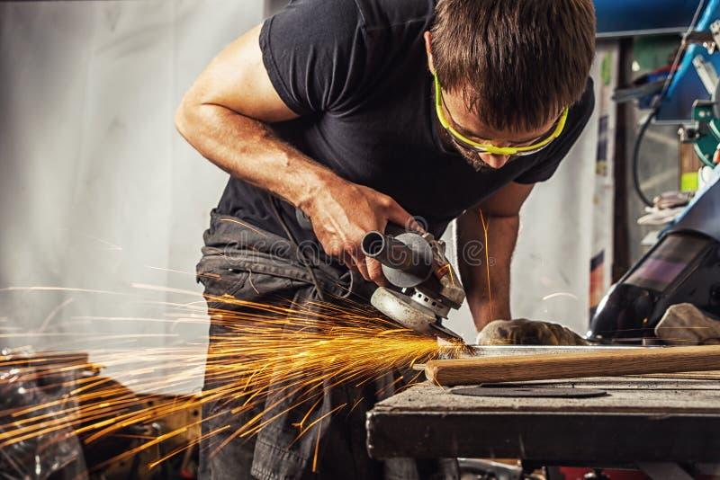 Reibendes Metall des Mannes mit einem Winkelschleifer lizenzfreie stockbilder
