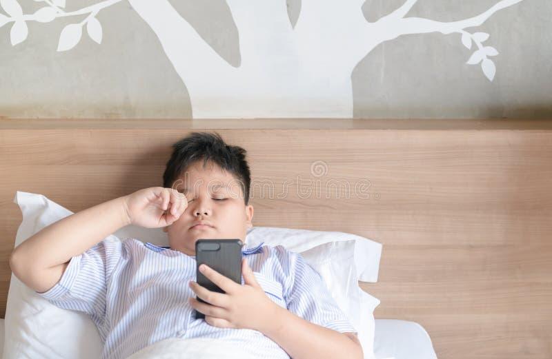 Reibungsaugen des Jungen nach Spiel Smartphone stockfotografie