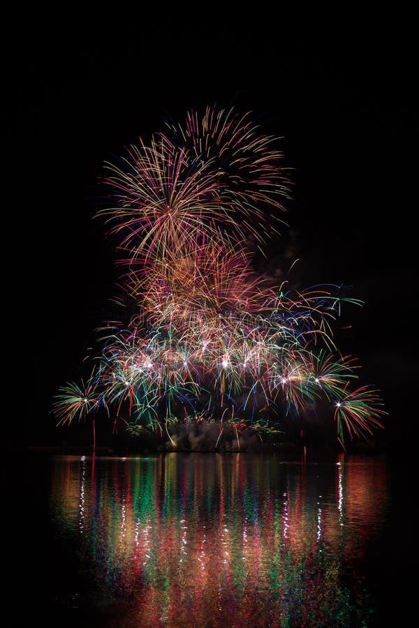 Reiche Feuerwerke voll von den Sternen über Oberfläche von Brnos Verdammung mit Seereflexion stockfoto